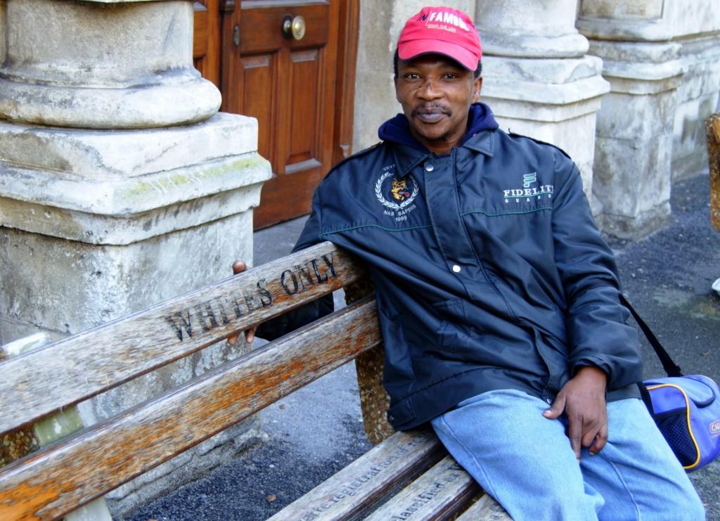En sort mand sidder på en bænk i Cape Town 2008. Bænken med teksten Kun Hvide er fra dengang Sydafrika var en apartheidstat.